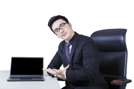 displaying: Image of confidence businessman sitting on the chair while displaying a laptop computer on the table