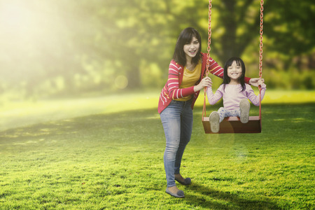 Portrait of cute daughter and young mother playing swing in the park while smiling at the camera