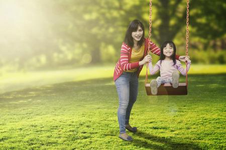 Portret van schattige dochter en jonge moeder spelen schommel in het park, terwijl lachend op de camera