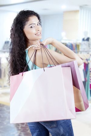 Portrait of young Indian female is holding shopping bags while smiling and looking at the camera in the store