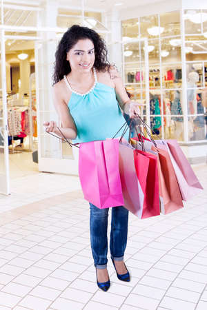 tienda de ropa: Portrait of indian female is smiling at camera while holding and opening shopping bags in the fashion center