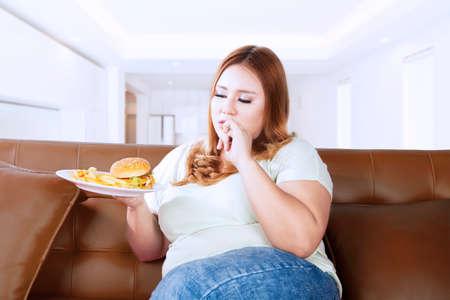 mujer gorda: Retrato de mujer con sobrepeso se ve con hambre y comer una comida basura mientras se está sentado en el sofá