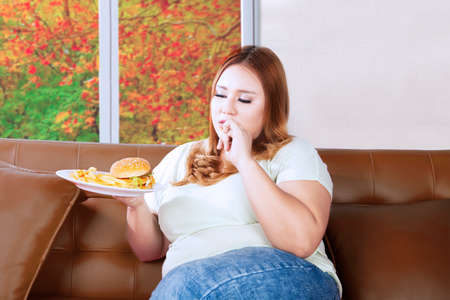 woman eating: Fat woman eating junk food on a plate while sitting on the couch with autumn background on the window