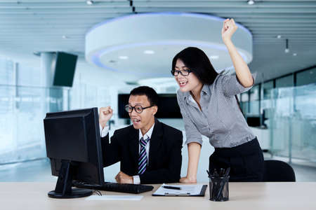 looking at computer: Portrait of businesswoman and her partner raising hands as their success expression in the office Stock Photo