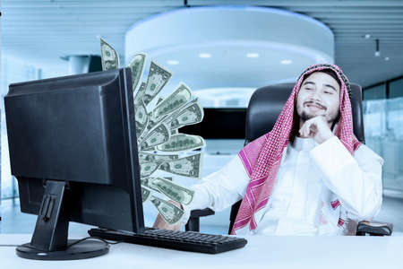 dinero volando: Portrait of arabian businessman looking at money flying out of monitor while sitting on the chair