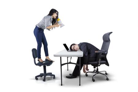 Foto de la joven gritando a su líder empleado cansada mediante el uso de un megáfono, aislado en fondo blanco Foto de archivo