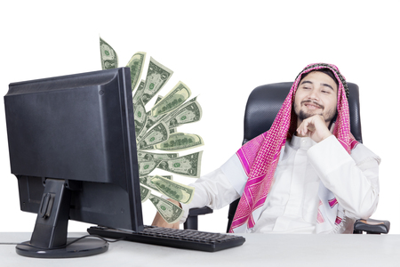 dinero volando: Muslim businessman looking at money flying out of monitor while sitting on the chair, isolated on white background Foto de archivo