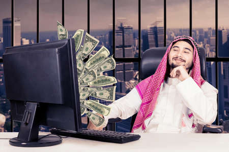 dinero volando: Portrait of proud muslim man looking at money flying out of monitor while sitting on the chair Foto de archivo