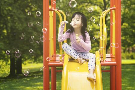 놀이터에서 쏜 비누 거품을 불고있는 동안 슬라이드에 앉아있는 귀여운 소녀