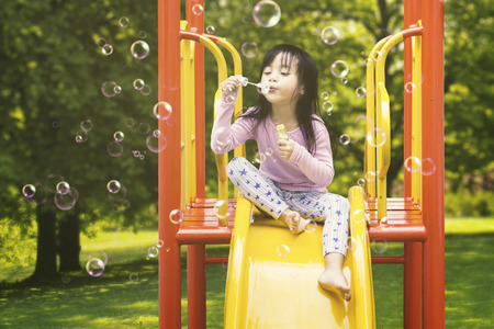 Cute little girl sitting on the slide while blowing soap bubbles, shot at the playground
