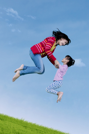 family playing: Little girl and young mother leaping on the air together while playing on the meadow Stock Photo
