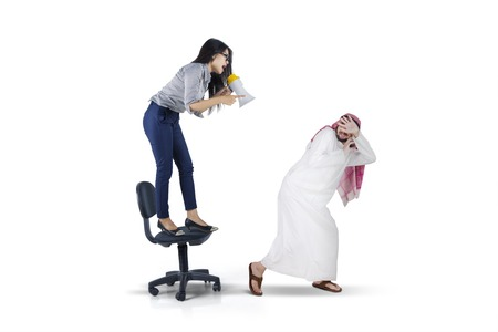 Picture of businesswoman yelling to her arabian subordinate with megaphone while standing on the chair, isolated on white background