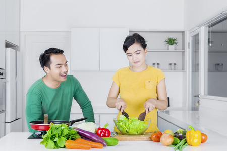 bean family: Young wife and her husband making salad on a bowl while standing in the kitchen Stock Photo