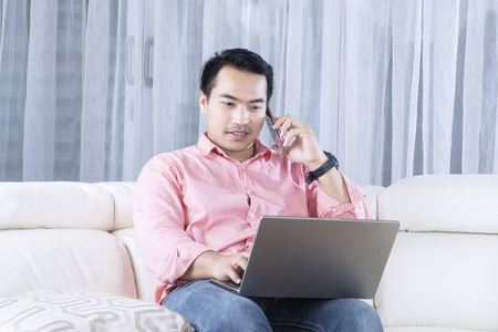 casual business man: Young man sitting on the couch while speaking on the mobile phone and working with a laptop