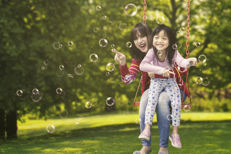 Cheerful little girl and her mother sitting on a swing while touching soap bubbles