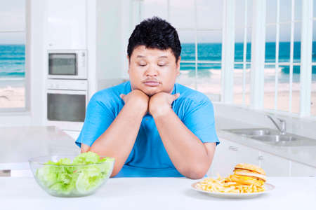 choose person: Overweight person looks confused to choose food, shot in the kitchen at home