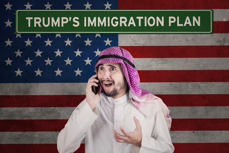 Shocked Arab businessman speaking on a mobile phone while standing in front of flag America with Trumps Immigration Plan word on a signboard