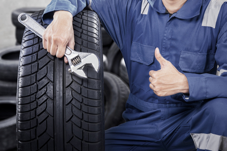 Close up of mechanic showing ok gesture with his thumb while holding a wrench Stock Photo