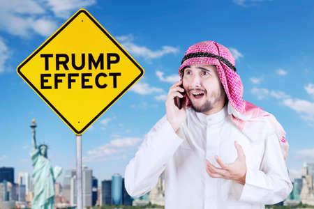desconfianza: El hombre de negocios árabe se ve sorprendido mientras que mira la palabra del efecto de Trump en un poste indicador y hablando en un teléfono móvil