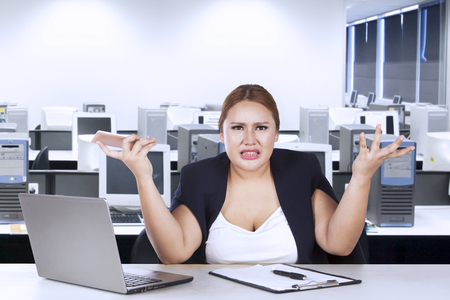 shrugs: Portrait of female entrepreneur confused with her job while shrugs her shoulder in the office Stock Photo