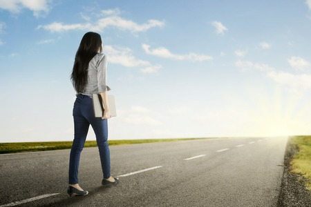 Back view of a young woman walks on the road to start her journey while holds a laptop
