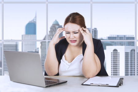 Portrait of female worker frustration with her job while holding her head in front of laptop Stock Photo