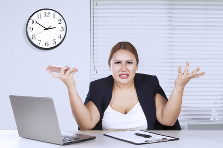 shrugs: Young businesswoman shrugs her shoulder while confused with her job in the office