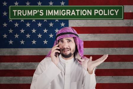 desconfianza: El empresario árabe parece confundido mientras habla por teléfono móvil de pie frente a una bandera estadounidense con la palabra de la política de inmigración de Trump