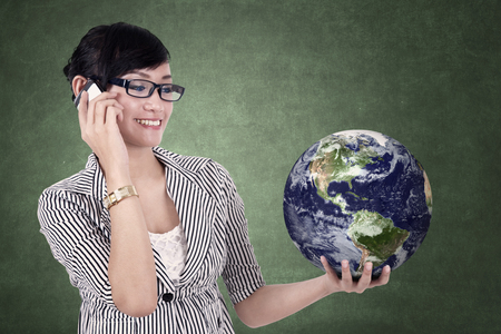 Young businesswoman holding a globe on classroom
