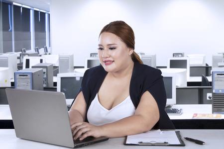 사무실에서 그녀의 책상 앞에 앉아있는 동안 노트북에 입력하는 여성 작업자의 초상화 스톡 콘텐츠