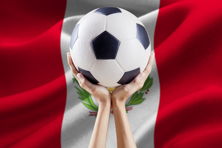Close up of two arms lifting a soccer ball with national flag background of Peru
