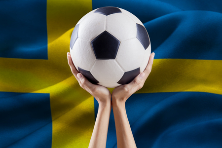 Close up of two arms holding a soccer ball with flag background of Sweden