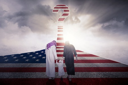 Back view of Muslim family walking together on the highway with USA flag and a question mark Stock Photo