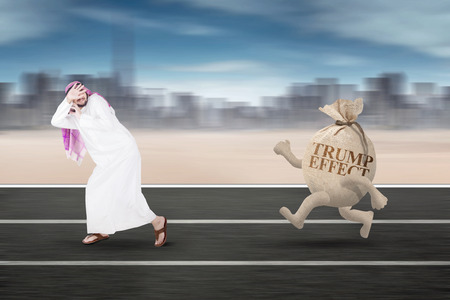 Image of money bag with the Trump word chasing Arabian businessman on the street Stock Photo