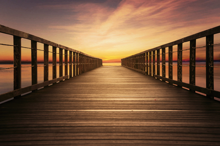 bridge in nature: Image of wooden pier with colorful sky on the beach at sunset time