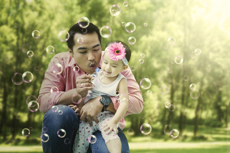 Photo of young father is blowing soap bubbles and playing with his daughter in the park