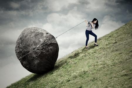 Beeld van jonge onderneemster die op de heuvel beklimt terwijl het trekken van grote steen met een ketting Stockfoto - 72216544