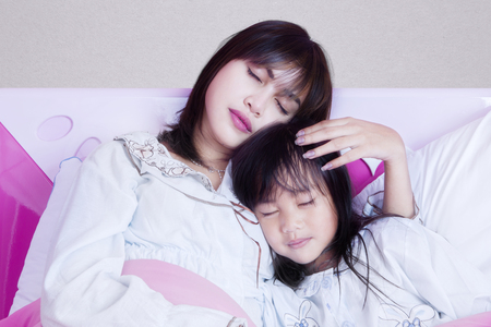 stroked: Portrait of a beautiful young mother and her daughter sleeping together on the bedroom at home
