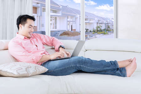young male: Portrait of handsome man typing on a laptop while sitting on the sofa