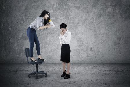 arrogancia: Cuadro de la mujer líder gritando a su empleado estresante con un megáfono mientras está de pie en la silla