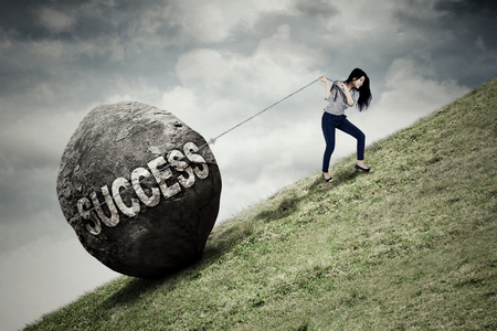 Portrait of beautiful businesswoman pulling big stone with success word while climbing on the hill Stock Photo
