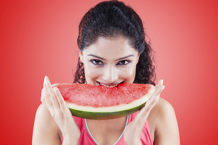 nip: Young woman biting a big slice of sweet watermelon while smiling and looking at the camera on the red background