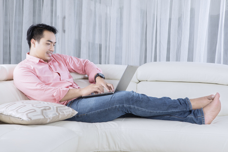 freelancers: Portrait of young male lying and relaxing on the couch while using a laptop in the living room