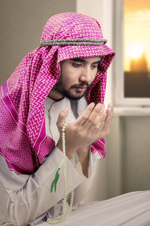 Portrait of devout man is wearing Islamic clothes while praying to the Allah at home Stock Photo