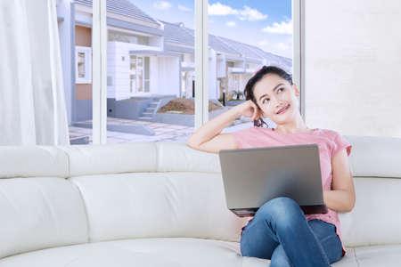 niña pensando: Retrato de la hermosa mujer que piensa una idea mientras está sentado en el sofá con el portátil