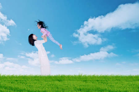 asian family outdoor: Picture of joyful young mother lifting her daughter up in the air, shot on the meadow Stock Photo