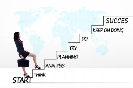 Photo of a young female entrepreneur walking upward on the stairs with strategy plan to success and world map background