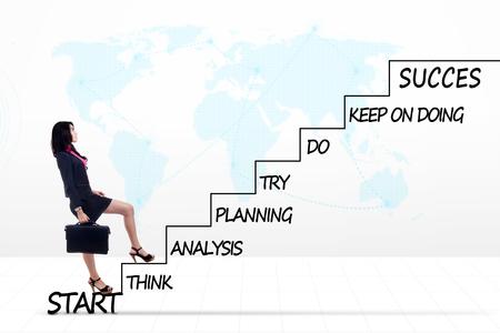 Photo d'une jeune femme entrepreneur marchant vers le haut sur les escaliers avec le plan stratégique de la réussite et de carte du monde de fond Banque d'images