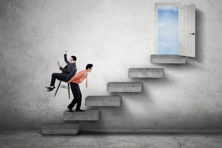 upward struggle: Male worker walking on the stair while carrying his boss through a doorway