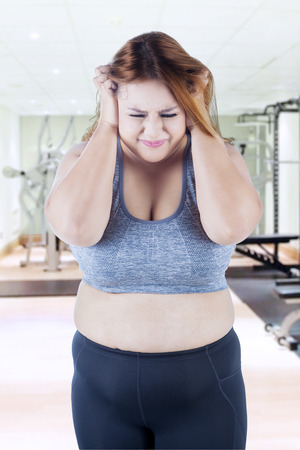 low self esteem: Picture of overweight woman looks frustrated, standing in the fitness center while scratching her head